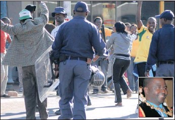 ?? PICTURE: MARK WING ?? Police keep a close eye on ANC demonstrators who gathered outside the Pietermaritzburg City Hall during the inauguration of the new council yesterday. They also fired stun grenades to disperse the group which was throwing tomatoes and rubbish at...
