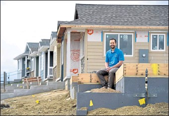 ?? JENNY SPARKS / Loveland Reporter-herald ?? Chris Zwakenberg, faith relations and volunteer director for Loveland Habitat for Humanity, poses for a photo Friday sitting on the foundation of a Habitat home with others in various stages of construction behind him in the 1700 block of Valency Drive in Loveland.