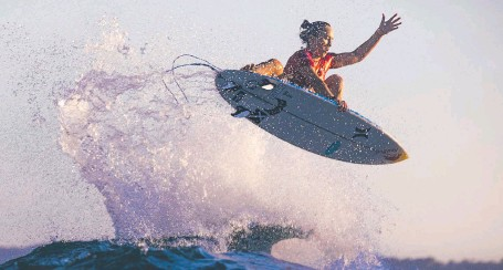?? GETTY IMAGES ?? Four-time world champion Carissa Moore of Hawaii pulls off a spectacular aerial manoeuvre at the Rip Curl Newcastle Cup yesterday