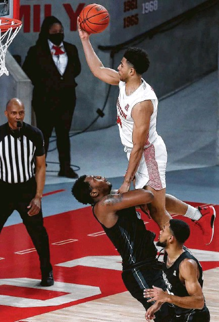 ?? Karen Warren / Staff photographer ?? Quentin Grimes, drawing a blocking foul from Central Florida's Jamille Reynolds, led UH with 18 points Sunday.