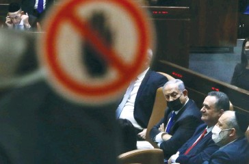 ?? (Marc Israel Sellem/The Jerusalem Post) ?? FORMER PRIME minister Benjamin Netanyahu is seen through a glass panel sitting in the Knesset seat as new leader of the opposition.