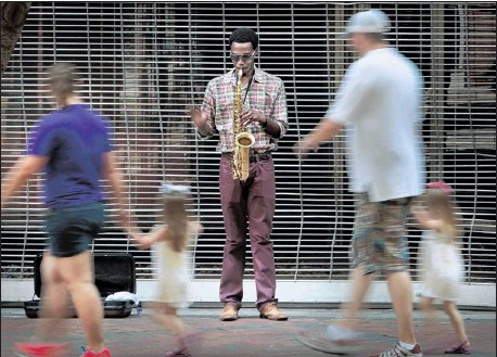 ?? JIM WEBER/THE COMMERCIAL APPEAL ?? Michael Starnes Jr. waves to pedestrians while performing Thursday afternoon on Main Street. Downtown is getting more crowded, according to a new study.