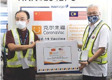 ??  ?? Senior Minister (Security Cluster) Datuk Seri Ismail Sabri Yaakob (right) receives the Sinovac vaccine from China's Ambassador to Malaysia Ouyang Yujing at Kuala Lumpur International Airport yesterday.