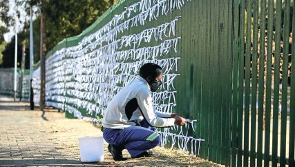 ?? Picture: Alaister Russell ?? Silva Cossa ties ribbons onto the fence around St James Presbyterian Church in Bedfordview, East of Johannesburg. The white ribbons represent people who have died from Covid-19.