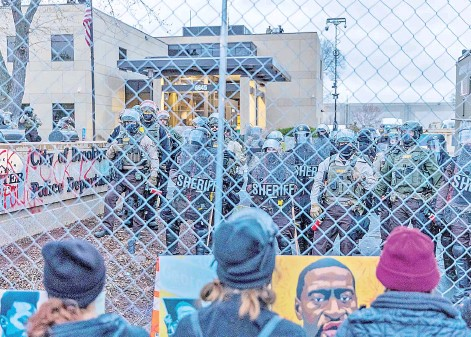 ?? — AFP photo ?? Sheriff officers stand guard outside the Brooklyn Centre police station as demonstrators stand on the other side of the chaink-link fence protesting the death of Wright.