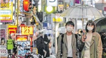?? FOTO: KYODO/DPA ?? Passanten in der japanischen Hauptstadt Tokio tragen Masken zum Schutz vor dem neuartigen Coronavirus: In Asien ist die Nutzung der Masken unumstritten, in Europa dagegen nicht.