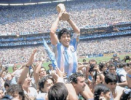 ?? CARLOFUMAGALLI/AP ?? Diego Maradona holds up his team's trophy after a 3-2 victory overWest Germany at the World Cup final soccermatch in 1986, atAtzeca Stadium inMexico City.