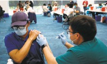 ?? Josie Lepe / Special to The Chronicle ?? Mariano Zelaya of Redwood City receives his shot from Carlos Martinez at the Facebook headquarters vaccination center.