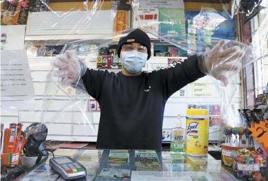 ?? PHOTO COLLABORATION SPÉCIALE, CAROLINE LEPAGE ?? Le propriétaire du dépanneur de Saint-Pie, David Sun, derrière une pellicule plastique installée devant sa caisse enregistreuse.