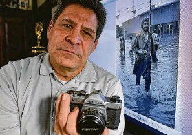 ?? Billy Calzada / Staff photographer ?? Brian Collister holds his father's Pentax camera, which his dad used as a news photographer. The photo in the background is of his father covering a flood.