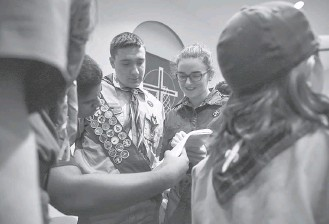 ?? JAHI CHIKWENDIU/THE WASHINGTON POST ?? From left, Joe Peters, William Calli and Julie Zylich chat before a Scouts BSA information session. Last month, the Girl Scouts filed a lawsuit against the Boy Scouts for creating unfair competition.