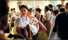 ?? WANG JING / CHINA DAILY ?? Doctors and nurses help transfer patients with the aid of the patients' family members at the First Affiliated Hospital of Zhengzhou University in Henan province on Wednesday.