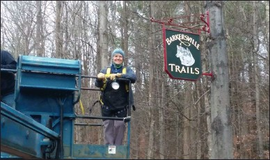 ?? PHOTO PROVIDED ?? Signmaker Kendra Schieber installs a sign for the newBarkersville Trails.