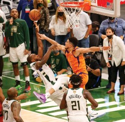 ?? (Reuters) ?? MILWAUKEE BUCKS forward Khris Middleton shoots over Phoenix Suns guard Devin Booker during the fourth quarter of the Bucks' 109-103 home victory in Game 4 of the NBA Finals. Middleton led the Bucks with 40 points, while Booker had 42 in a losing effort.