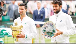 ??  ?? Serbia's Novak Djokovic holds the winner's trophy, with Italy's Matteo Berrettini standing beside him with the runners-up trophy for the men's singles final match on day thirteen of the Wimbledon Tennis Championships in London, Sunday, July 11, 2021. (AP)