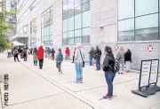 ??  ?? NER­VOUS WAIT: Peo­ple queue at the Women's Col­lege Covid-19 test­ing fa­cil­ity in Toronto.