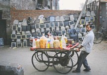 ?? ALTAF QADRI/ASSOCIATED PRESS ?? A snack vendor pushes his cart past disused computer monitors stacked up on a roadside in New Delhi on Saturday. Salvagers harvest metals such as copper, gold and aluminum from old monitors and sell them, but they risk exposure to toxic materials such as mercury.