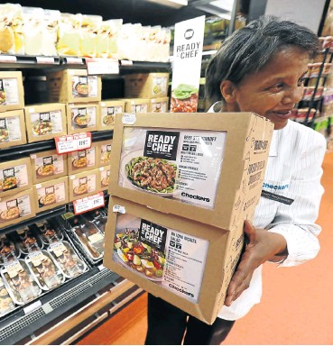 ?? Picture: Esa Alexander ?? Anathi Nxqzonke with packs of the prepare-yourself meal kits at Checkers in Canal Walk, Cape Town. Such convenient meal kits are becoming popular since their introduction in SA.