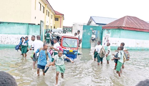 ?? Photo: NAN ?? Pupils of Bayelsa State Model Primary and Secondary School wade through flood water within their school's premises in Yenagoa yesterday