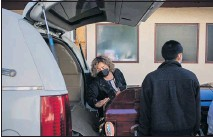 ?? PHOTO BY ALEX WELSH ?? Magda Maldonado, owner of the Continenta­l Funeral Home, wipes dust off a casket. She has taken part in as many as 13 funerals in a day.