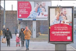 """??  ?? People walk past posters reading """"Do not risk everything that is dear to you. Get vaccinated against coronavirus"""" in St. Petersburg, Russia. (AP/Dmitri Lovetsky)"""