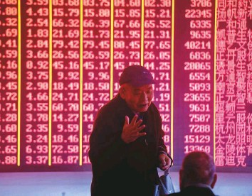 ?? AFP ?? Investors at a brokerage in Hangzhou in China's eastern Zhejiang province. Shanghai markets fell 0.6 per cent yesterday.