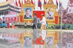 ??  ?? ABOVE Men walk past portraits of Xi Jinping and Cambodian King Norodom Sihamoni prior to the Chinese president's visit to Phnom Penh in October last year.
