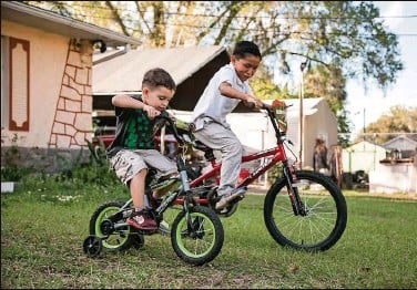 ?? Photos by CINDY KARP   Washington Post ?? Pascual, right, races his younger foster brother in their front yard in Kissimmee.
