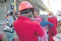 ??  ?? SOFTER SIDE Red Ant William Mahlalela comforts S'nehlanhla Fortunate Majoro, whose mom was evicted from Fattis Mansions.