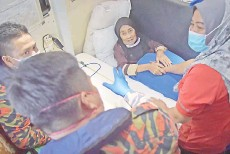 ??  ?? Salmah (second, right) and her only daughter Noredah inside the Malaysian Maritime Enforcement Agency patrol boat to Labuan at the Menumbok jetty yesterday. - Bernama photo