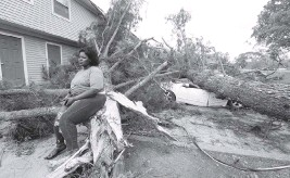 ?? THOMAS WELLS The Northeast Mississippi Daily Journal via AP ?? Myesha Gore sits on the trunk of a shattered tree Monday after another tree crushed her car in Vardaman, Miss., during Sunday's severe weather.
