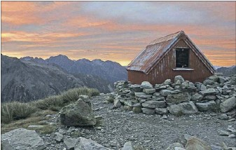 ?? Jeremy Cronon/The New York Times ?? Sunset glows on tiny Sefton Bivvy, a hut nestled beneath the Tewaewae Glacier and where the writer couldn't stand completely.