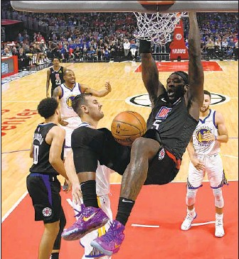 ?? Harry How Getty Images ?? MONTREZL HARRELL SLAMS home a dunk during a loss to Golden State in Game 4 on Sunday afternoon at Staples Center. Harrell's efficiency on the pick-and-roll has been a key for the Clippers.