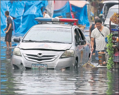 ??  ?? FLOODED: Vendors and police in Quezon struggle with the aftermath of the typhoon which left at least six people dead. Picture: Aaron Favila