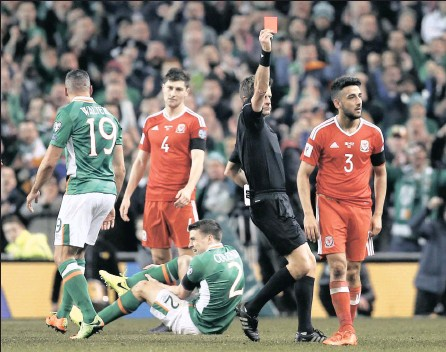 ?? PICTURE: REUTERS ?? DOUBLE LEG BREAK: Wales' Neil Taylor is sent off by referee Nicola Rizzoli as Republic of Ireland's Seamus Coleman lies injured at Aviva Stadium, Dublin.