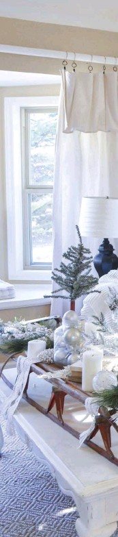??  ?? THE FRONT ROOM is a neutral haven, filled with comfy pillows, faux greenery and repurposed finds, including a vintage sled and an old door. The faux Christmas tree is adorned with neutral ribbon and ornaments to keep it classic and minimal.