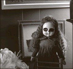 """??  ?? An antique doll is painted for the Mexican """"Day of the Dead"""" celebration. Wilson made some of the items in the house, such as a box holding a bloodsplattered voodoo doll on a coffee table."""