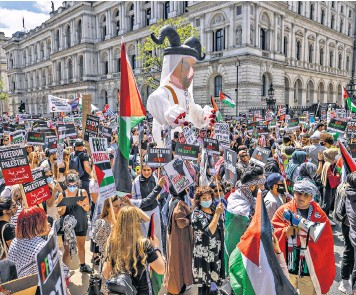 ??  ?? Some placards drew parallels between Hitler's Germany and Israel at the Free Palestine protest outside Downing Street yesterday