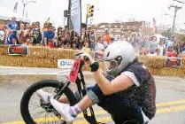?? IAN MAULE/Tulsa World ?? A racer tries to avoid water balloons during Boulder Dash tricycle race through the Arts District on Saturday.