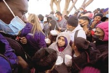 ?? GREGORY BULL/ASSOCIATED PRESS ?? Asylum seekers receive food as they wait for news of policy changes in February at the border in Tijuana, Mexico.