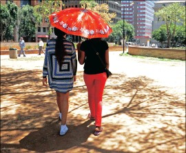 ?? PICTURE : SIMONE KLEY ?? SEEKING RELIEF: Two women walk through Joburg's CBD under the shade of an umbrella as the searing heat pushed the mercury to 35°C last week.