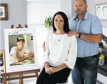 ?? Picture: Alaister Russell ?? Julie and Tim Edwards next to a portrait of their son, Joshua, who died after being shot while visiting a friend in early January. No arrests have been made.