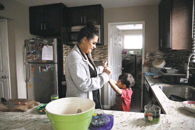 ?? Lea Suzuki / The Chronicle ?? Adrianna Wolfe clasps hands with son Leonardo RamirezWolfe, 6, after he blows out a candle on the kitchen counter of their new home in Pacifica. They lost their home in Millbrae to fire.