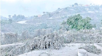 ?? — AFP file photo ?? This handout image shows a view from the Belmont Observatory in Saint Vincent as the eruption at La Soufriere continues, as the volcano is obscured by the ashfall and deposits can be seen on surrounding vegetation and houses.