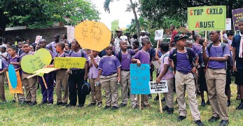 ?? FILE ?? The boys of Yabnel Care Centre holding signs during a recent march against child abuse.