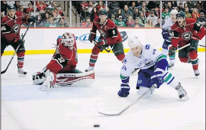 ?? HANNAH FOSLIEN/ GETTY IMAGES ?? Canucks forward Byron Bitz dives after the puck during his team's 5- 2 win over the Minnesota Wild at the Xcel Energy Center in St. Paul, Minn., Thursday. Bitz has a goal and two assists in three games since being called up from the AHL Chicago Wolves.