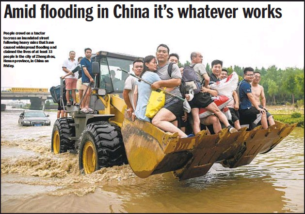 ??  ?? People crowd on a tractor to cross an inundated street following heavy rains that have caused widespread flooding and claimed the lives of at least 33 people in the city of Zhengzhou, Henan province, in China on Friday.