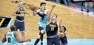 ?? Jared C. Tilton, Getty Images ?? Charlotte's LaMelo Ball drives to the basket against Denver's Nikola Jokic during the third quarter Tuesday night at Spectrum Center.