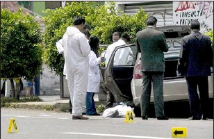 ?? FERNANDO CASTILLO/AFP/GETTY IMAGES ?? Mexican police personnel examine the car of one of Mexico City's top police officers, Esteban Robles, who shot dead by hitmen in May. He was the the fourth top police authority slain in a 10-day period, as the toll from a rising organized crime wave...