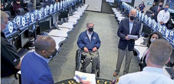 ?? — AFP photo ?? Biden and Texas Governor Greg Abbott (centre) listen to officials at the Harris County Emergency Operations Center in Houston, Texas.